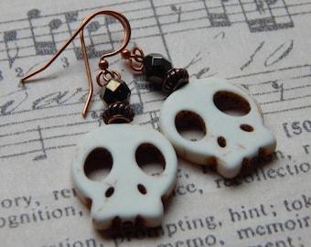 White magnesite skull-shaped earrings.