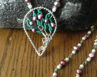 Cultured (magenta-coloured) pearl with green seed bead pendant in wire wrapped wire teardrop.