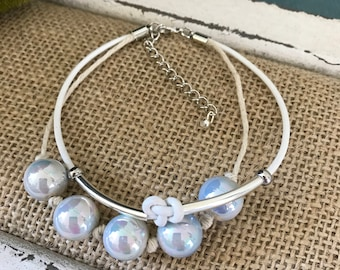 White leather bracelet with vintage iridescent blue pearls .  Has an extender style clasp .