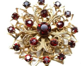 "60s Rhinestone brooch, Filigree with garnet glass, star/flower design. 1.25""."
