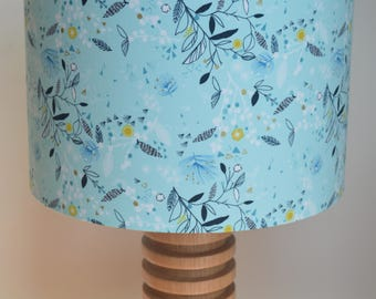 Handmade drum lampshade with repeated flowers and foliage in sky blue, white, navy and gold