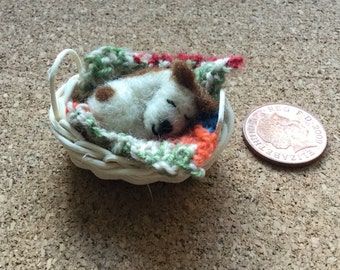 Miniature needle felted dog in a hand made basket with a tiny knitted blanket. This miniature is on a scale of 1:12