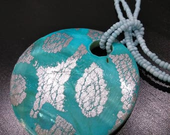 Teal and silver shell charm on a teal seed beaded multi strand necklace
