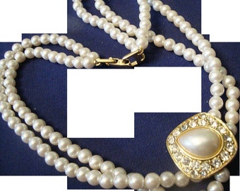 VINTAGE double strand of 6mm faux pearls with a gold tone medallion encircled by rhinestones