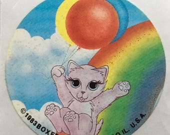 Kitty sliding down rainbow holding balloons sticker, 1983