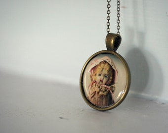 Photo Pendant Necklace of an Antique Porcelain Doll Named Claudia Wearing A Pink Bonnet
