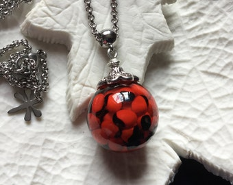 Red and black seeds and resin pendant bubble mounted on stainless steel necklace.