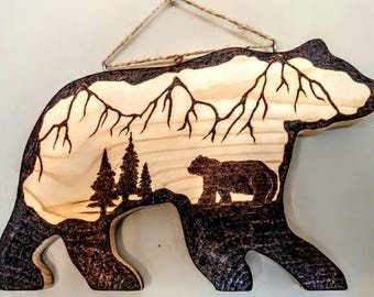 "A rustic, woodburned bear, in bear country, on 11""×6""×1"" bear cutout wall hanging"