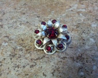 Vintage gold tone metal and red crystal floral motif brooch