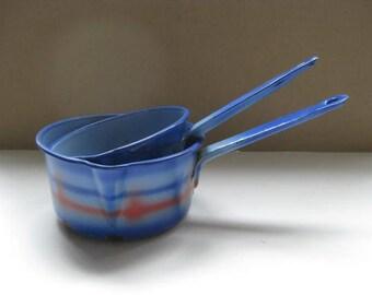 Two French enamel saucepans in dark blue, light blue en red color.