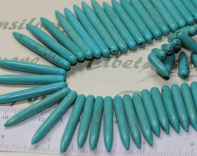A strand of Graduated 45x5mm to 12x5mm Point Round Spike Turquoise Dyed Magnesite.