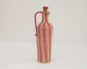 Vintage glass bottle dressed in red plastic and white Folk, 1960's