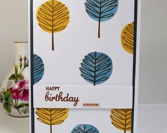 Birthday card with blue and yellow stylized trees and copper heat embossed sentiment
