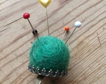A green felt pin cushion ring