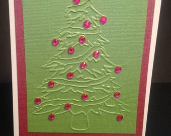 A card made with green pearl cardstock that has a Chritmas tree embossed on it and accented with red rhinestones