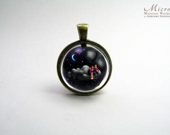 Miniature World pendant. A romantic fantasy scene of a man and woman are sitting on a cloud travelling through the starry night.