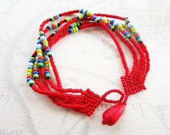 "Bracelet weaved in seed type ""Maasai"", red and multicolor"