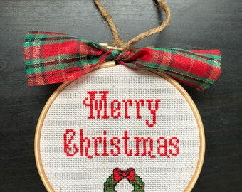 Finished framed cross stitch christmas ornament merry christmas with christmas wreath framed in wooden hoop with decorative bow