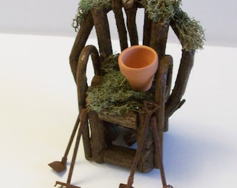 Miniature moss covered grapevine chair with garden tools and a terra cotta pot.