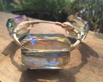 Wire-wrapped bangle bracelet with enerald colored stones