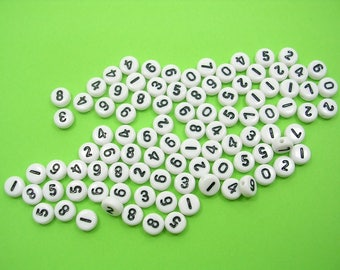 100 white round beads with 7mm black figure