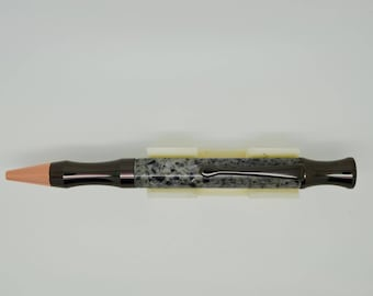 Hand turned rocket bullet twist pen in Mistral Zircona Corian solid surface material with gun metal finish.