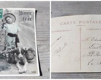 Vintage Antique old French 1900 postcard / dog & child/ dog holding a basket of flowers/ greetings / Bonne année