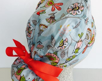 Ponytail Scrub Cap scrub hat featuring a light blue material with birds and flowers in red pink white and green with a matching red ribbon