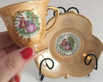 Miniature mid century courting couple teacup with gold gilding. Tiny peach elegance teacup with leaf shaped saucer.