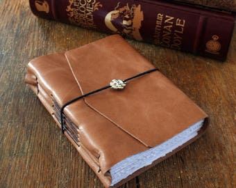"""Leather Journal . Louisa May Alcott: """"She is too fond of books and it has turned her brain."""" handbound . honey brown/tan (320 pgs)"""