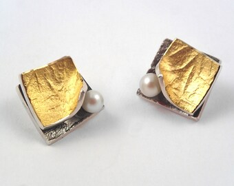 There are pearls between the pages of a book! Modern design, rough surface, stylish gold silver earrings with a pearl.