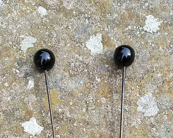 Large black glass topped edwardian hat pins.