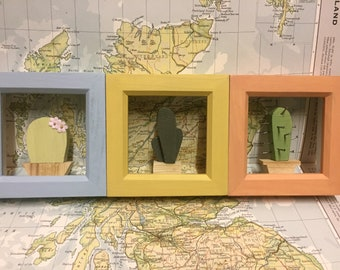 A set of three wooden cactuses in frames