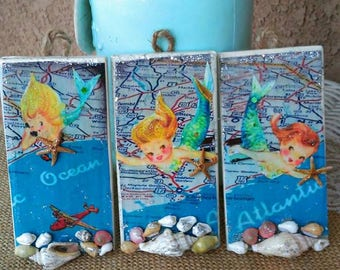 Darling trio set of baby vintage mermaids with maps on hanging tiles.