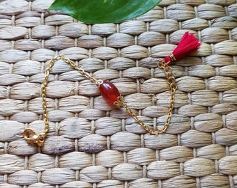 Golden bracelet with red agate gemstone and tassel.