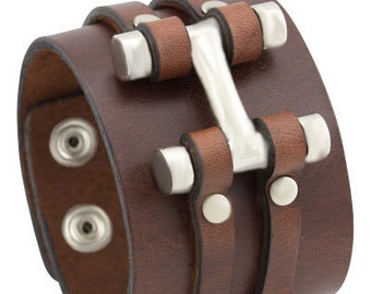 Thick brown leather bracelet with 2 studded strips and a large metal H-shaped decoration, Handmade adjustable wide leather cuff bracelet