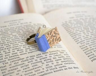 Anello con libro blu e foglie disegnate . Anello con libro in miniatura. Regalo per scrittori, lettori, librai