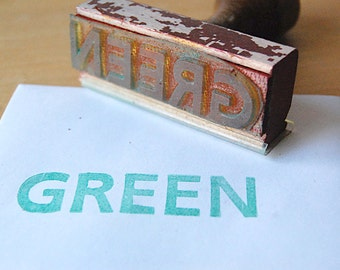 Vintage Wood Rubber Stamp of the Word Green in All Capital Letters Graphic Design.