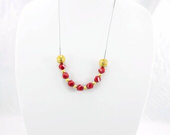 Long Necklace Made With Red Glass Beads And Golden Metal Beads