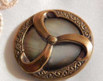 Mother of Pearl Set in Brass with Three Ribbon Swirls
