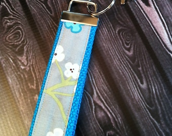 Grey and turquoise cherry blossoms fabric key fob wristlet on turquoise cotton webbing with swivel lobster clasp