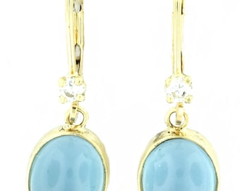 A pair of oval cabachon Aquamarine and diamond earrings set in 14k yellow gold bezel set leverbacks.