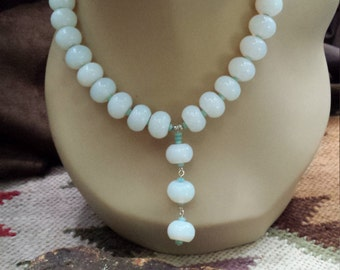One strand beaded necklace made with opulite and small sea green glass beads with center drop