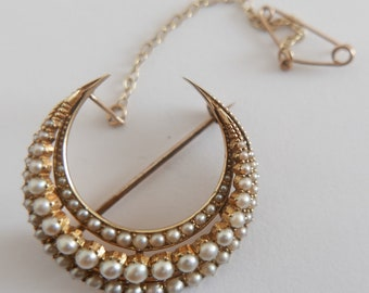 Antique Victorian Gold enclosed Crescent Seed Pearl Brooch with safety pin and set with 3 rows totalling 65 pearls.