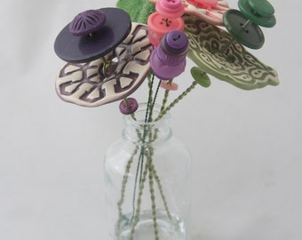 pink, green, and purple button flower bottle bouquet