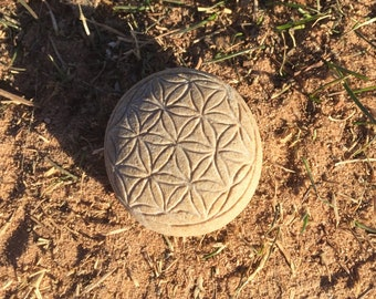 Hand carved stone with flower of life on a surface