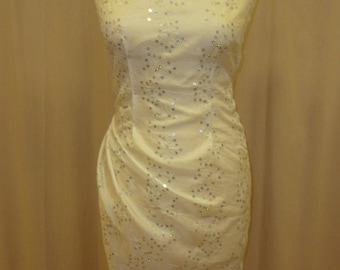 Slightly wrinkled white polyester with silver sequin embroidery