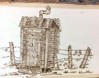 Outhouse by barb wire fence