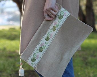 Handmade, beige-toned Clutch with floral embellishment.