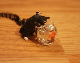 Kitty cat is playing with goldfish in a fish bowl necklace